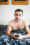 Attractive young man with a beard using a smartphone and texting while lying on his bed. Attractive man with a beard using a smartphone and texting while lying Royalty Free Stock Images
