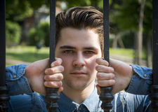 Attractive young man behind bars of metal gate Royalty Free Stock Image