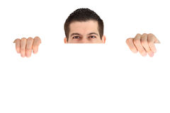 Attractive young man  behind blank banner. Attractive young man smiling behind blank banner Stock Photo