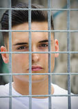 Attractive young man behind metal or steel grid Royalty Free Stock Images