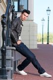 Attractive young man in black leather jacket sitting outdoors Royalty Free Stock Image