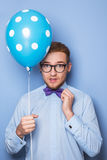 Attractive young man with a blue balloon in his hand. Party, birthday, Valentine. Studio portrait over blue background Royalty Free Stock Photography