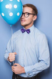 Attractive young man with a blue balloon in his hand. Party, birthday, Valentine. Studio portrait over blue background Stock Photography