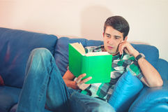 Attractive young man with the book on a couch Royalty Free Stock Image