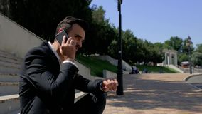 Attractive young man businessman with a beard sitting in a park on a concrete staircase and talking on the phone, then looks at stock footage