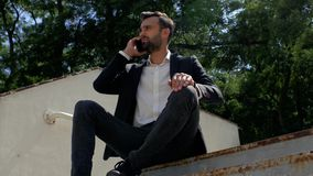 Attractive young man businessman with a beard sitting in a park on a concrete staircase and talking on the phone, then looks at stock video