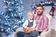 Attractive young man is celebrating Christmas with. Handsome father is sitting on chair near New Year fir-tree. He is holding his child on his knees and Stock Photos