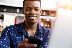 Attractive young man with cellphone and laptop in cafe. Close up portrait of attractive young man with cellphone and laptop in cafe royalty free stock photography