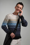 Attractive young man on cellphone, smilling. Stock Photo