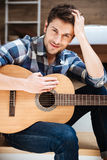 Attractive young man in checkered shirt with guitar Royalty Free Stock Photos