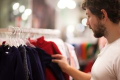 Attractive young man choosing baby clothes. Attractive young father at the kids apparel shop, bying clothes for his child Royalty Free Stock Photos