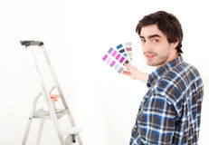 Attractive young man choosing color of his flat Stock Images