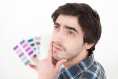 Attractive young man choosing color of his flat Royalty Free Stock Photos