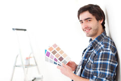 Attractive young man choosing the color of his flat Stock Photos