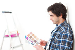 Attractive young man choosing the color of his flat Royalty Free Stock Photography