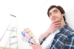 Attractive young man choosing the color of his flat Royalty Free Stock Images