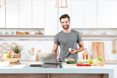 Attractive young man cooking with mixing bowl stock photos