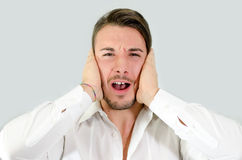 Attractive young man covering his ears, irritated Stock Photos