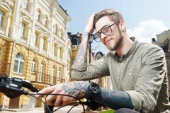Attractive young man is cycling across city Stock Images