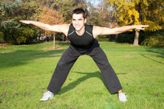 Attractive young man doing exercise in park Stock Image