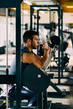Attractive Young Man Doing Heavy Weight Exercise For Biceps On Machine In A Gym.  Royalty Free Stock Photos