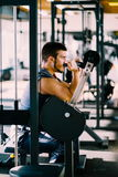 Attractive Young Man Doing Heavy Weight Exercise For Biceps On Machine In A Gym.  Stock Image