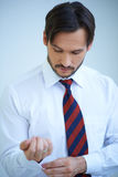 Attractive young man doing up his shirt cuffs. Attractive young man looking down at his arm doing up his shirt cuffs as he dresses ready for a day at the office Stock Photos