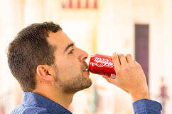 Attractive young man drinking a Coca-Cola can Stock Photo