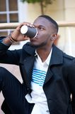 Attractive young man drinking coffee outside Stock Photos