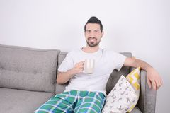 Man drinking coffee. Attractive young man drinking coffee and relaxed on couch. Indoors Stock Photos