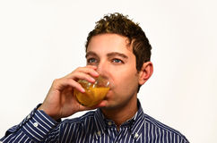Attractive young man drinking fruit juice. Good looking guy drinking fruit juice from a glass,  on white Royalty Free Stock Images