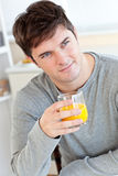 Attractive young man drinking orange juice. In the kitchen at home Stock Photo