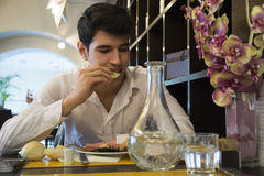 Attractive young man in elegant restaurant eating Royalty Free Stock Photos