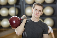 Attractive Young Man Exercising With Kettlebell In Gym Stock Photography