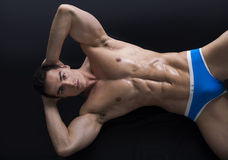 Attractive young man on the floor with muscular ripped body Royalty Free Stock Photography