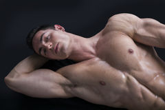 Attractive young man on the floor with muscular ripped body. Attractive young muscle man laying on the floor with muscular ripped body Royalty Free Stock Images