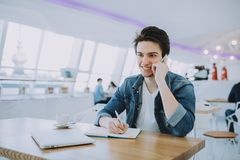 Attractive young man or freelancer with mobile is sitting in cafe Stock Photo