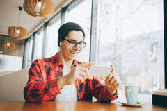 Attractive young man or freelancer is sitting in cafe and watching video stock image