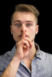 Attractive young man gesturing Hush or Silence  Royalty Free Stock Image