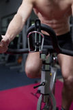 Attractive young man in gym on bike Stock Images
