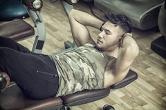 Attractive young man in gym exercising abs Stock Photo