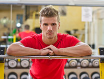 Attractive young man in gym resting on barbell Stock Images
