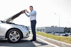 Attractive young man has some troubles with his. Cheerful businessman is opening car hood. He is checking the state of engine. He is smiling and looking at the Royalty Free Stock Photo
