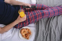 Man having breakfast in bed. Attractive young man having breakfast and watching tv in bed. Indoors Royalty Free Stock Photography