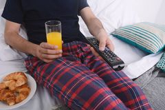 Man having breakfast in bed. Attractive young man having breakfast and watching tv in bed. Indoors Royalty Free Stock Images
