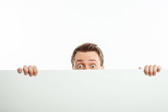 Attractive young man is hiding behind white wall Stock Photo