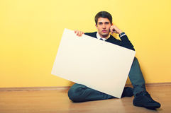 Attractive young man holding a blank billboard Royalty Free Stock Images