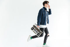 Attractive young man holding boombox. Looking aside. Image of attractive young man wearing glasses posing isolated over white background and holding boombox royalty free stock photos