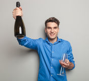 Attractive young man holding a bottle of champagne Stock Photos