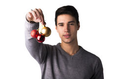 Attractive young man holding Christmas tree balls Royalty Free Stock Photos